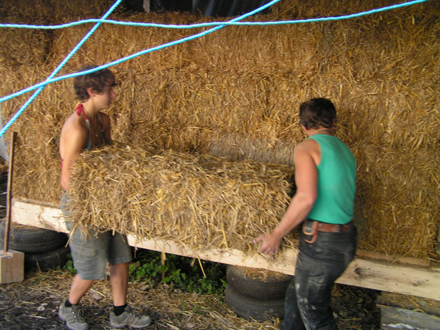 Rae and Anna taking a bale into the house