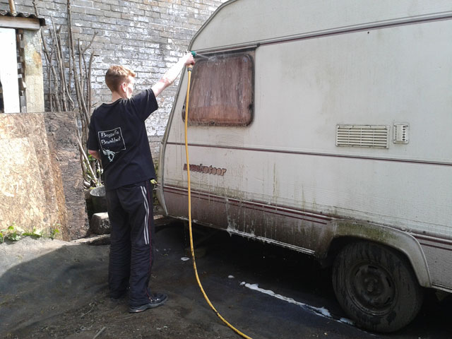 Lucy washing the caravan